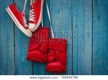 Red shoes and red boxing gloves hanging on a rope on a blue wooden old wall