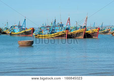 MUI NE, VIETNAM - DECEMBER 25, 2015: Fishing schooners in the Fish harbor of the village of Mui Ne early in the morning