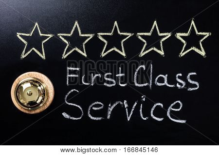 First Class Service With Service Bell Of Restaurant On Blackboard