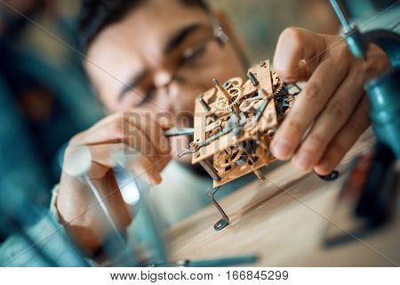 Close up portrait of a watchmaker at work.