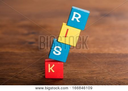 Close-up Of Risk Word On Stack Of Falling Cubes