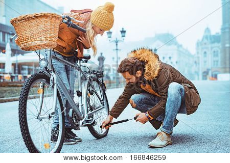 Close up of loving couple riding on bike in the city.Young man is filling his bike with air.