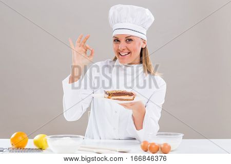Beautiful female confectioner is showing ok sign while holding slice of cake.