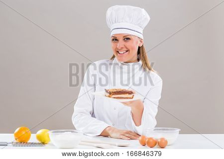 Beautiful female confectioner is showing slice of cake while sitting at the table