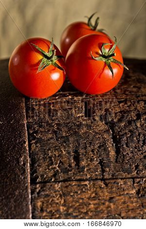 three tomatoes on the dark wooden background