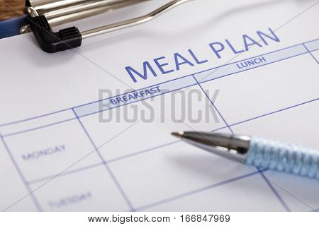 Close-up Of Pen With Meal Plan Form