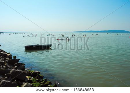 Vacationers at hot summer evening lake Balaton Hungary.