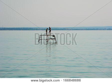 Boys on the pontoon Lake Balaton at summer evening Hungary.