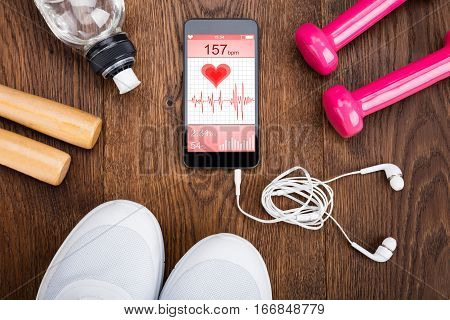 Exercise Equipment With Mobilephone Showing Health Application On Wooden Floor