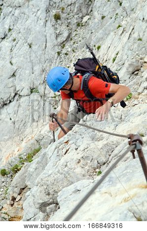 Mountaineer climbing up the steepy mountain in summer.