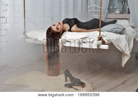 Beautiful girl  lying on  hanging bed suspended from the ceiling. Her hair hanging down .White loft interior.