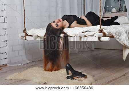 Beautiful girl  lying on  hanging bed suspended from the ceiling. Her hair hanging down .White loft interior with fog.