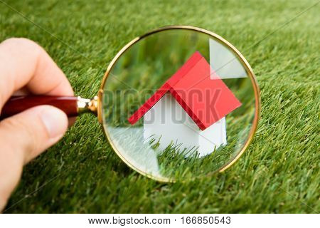 Person Hands With Magnifying Glass Inspecting A Model House On Grassy Field