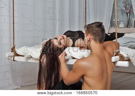 Young couple lying on  hanging bed suspended from the ceiling . They are looking at each other. White loft interior.
