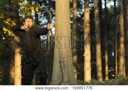 Archer in black kimono is aiming with traditional bow and arrow in the forest.