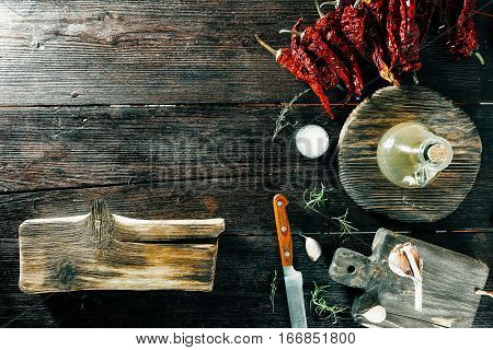 Various spices and condiments on rustic cutting boards. Knife and a board for text