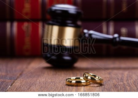 Close-up Of Wedding Rings With Gavel On Wooden Desk In Courtroom
