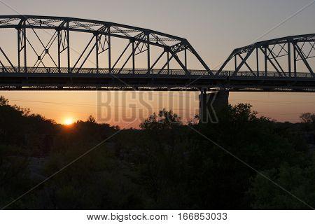 Silhouette of the bridge over the Llano River in central Texas at sun down.