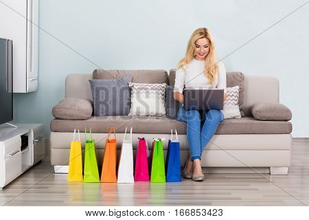 Woman Sitting On Couch With Shopping Bags Shopping Online Using Laptop At Home.
