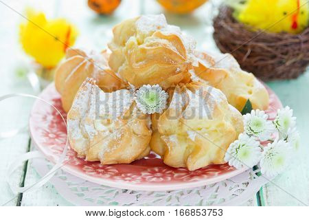 Easter dessert cream puffs with filling and powdered sugar on festive decorated Easter table