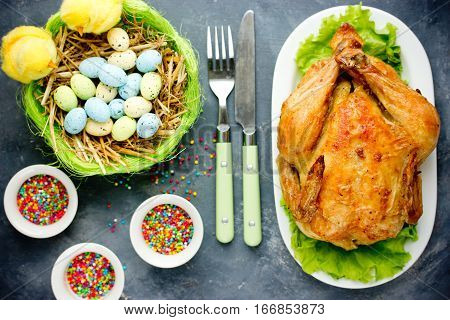 Easter dinner idea - whole roast chicken on Easter table with Easter eggs in nest top view
