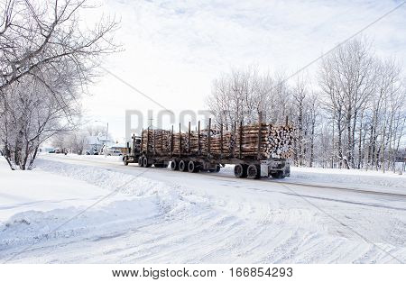 An eighteen wheel truck hauling a load of cut logs down a street through a small town in winter