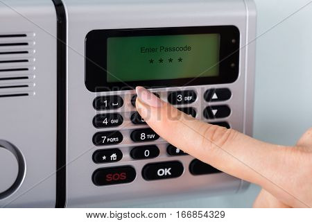 Close-up Of Person Hand Entering Code On Keypad Of Home Security Alarm