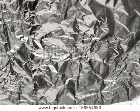 Silver wrinkled wrapping foil texture for background. Crumpled aluminium shiny metal pattern.