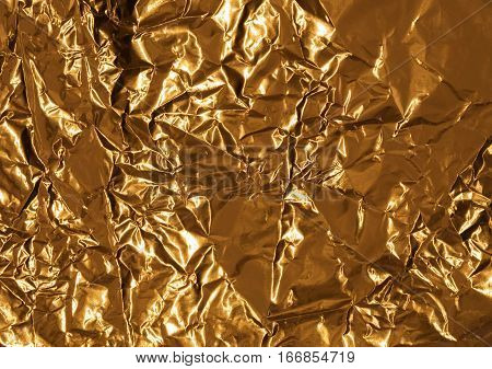 Golden wrinkled wrapping foil texture for background. Crumpled aluminium shiny metal pattern.