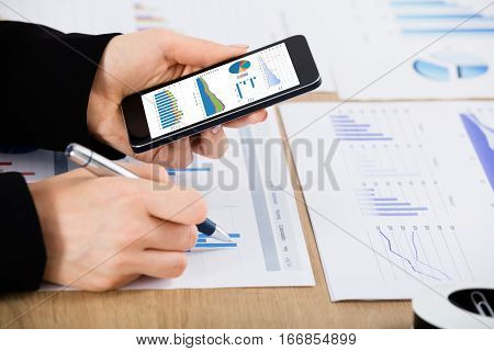 Close-up Of A Businesswoman With Mobilephone Working On Financial Graph At Office Desk