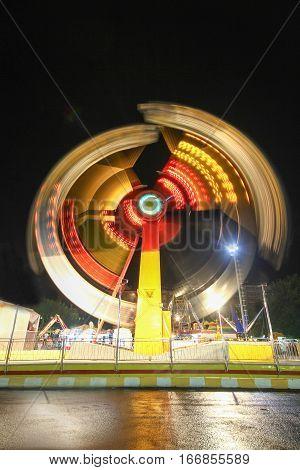 Amusement park at night - ferris wheel in motion