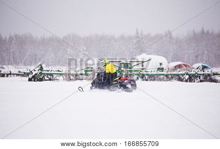A young man riding a snowmobile with agriculture equipment in the background in a farm yard in winter with snow falling