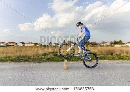Jugendlicher übt Tricks Sprünge mit dem Bike auf der Strasse