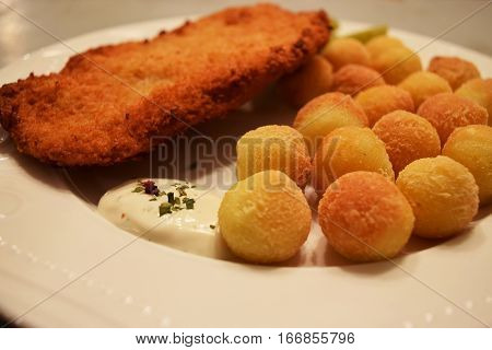 Chicken breast in breadcrumbs on a white plate