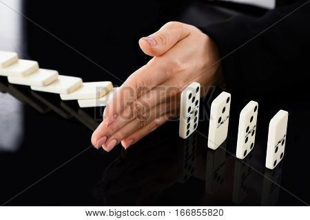 Close-up Of A Businesswoman Hand Stopping Dominoes From Falling On Office Desk. Risk Prevention Concept