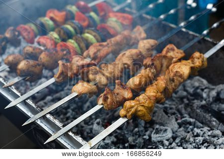 Raw kebab grilling on metal skewer. Meat roasting at barbecue with vegetables. BBQ fresh beef chop slices. Traditional eastern dish, shish kebab. Grill on charcoal and flame, picnic, street food