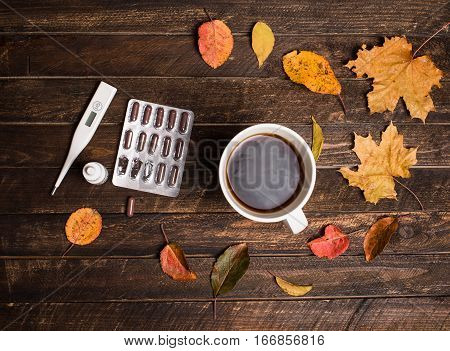 Hot tea pills nasal drops thermometer and autumn leaves on rustic dark wooden background. Top view. Fall and health care.
