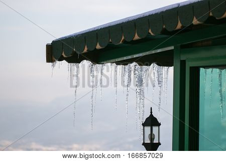 Winter season scene. Icicles on the roof. cold weather concept. Frozen icy down pipe waterspout.