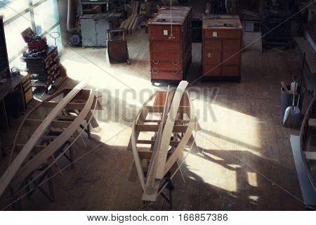 Vintage shipbuilding workshop with a bouats in construction process