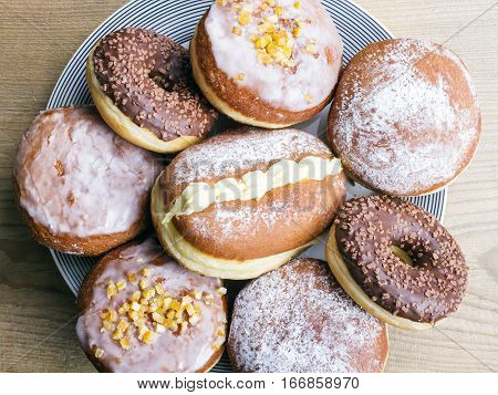 tasty donuts on a platter wooden background
