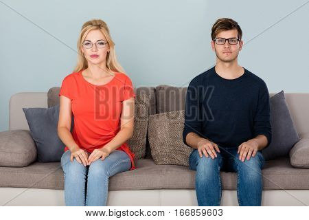 Portrait Of Man And Woman Wearing Glasses Sitting On Couch At Home