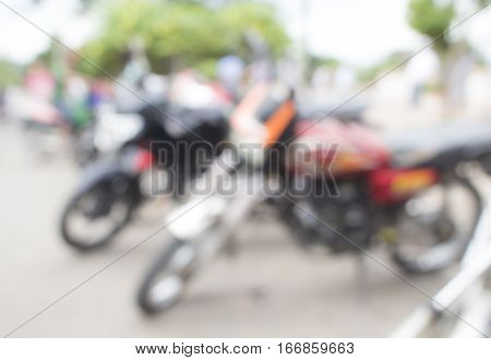 Abstract blur background with bikes on parking. Street life blur photo for background. Parked motorcycles in blur. City bokeh illustration. Defocused image of motorbikes parking. Transport blur photo