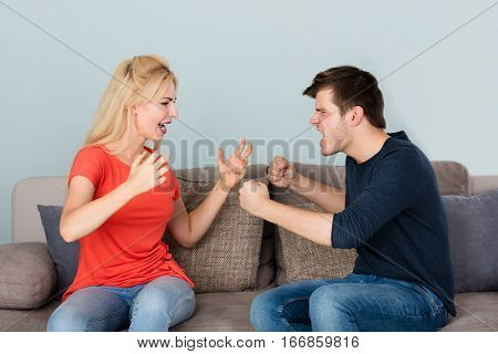 Sad Couple Sitting On Couch Arguing And Fighting With Each Other At Home