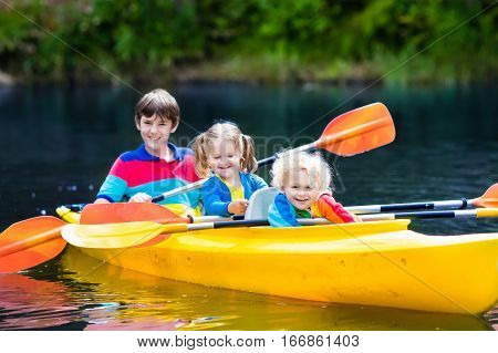 Happy family with three kids enjoying kayak ride on beautiful river. Little girl toddler boy and teenager kayaking on hot summer day. Water sport and camping fun. Canoe and boat for children.