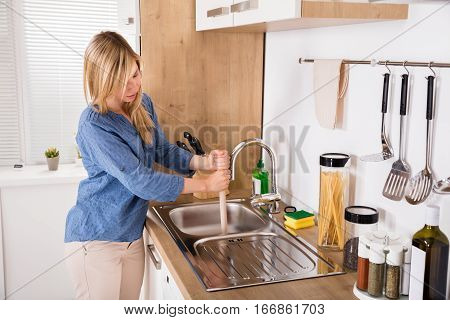 Young Woman Using Plunger In Blocked Kitchen Sink To Unclog Drain At Home