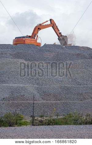 A large excavator loads gravel from a moutain of gravel rock which it is situated on.