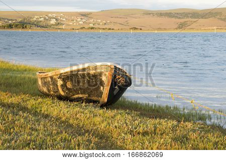 An old hull of a ski boat lies on the green grass of a river bank.