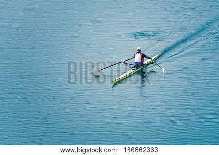 Single scull rowing on lake , toned image