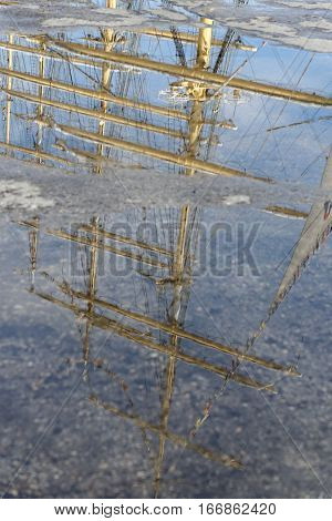 Reflection of a mast of a sailing ship in a paddle.