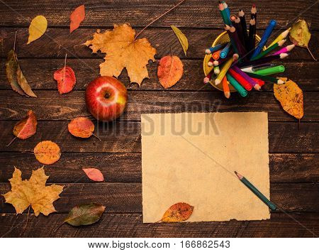 A pencil on the empty vintage paper an apple and autumn leaves on wooden table. Back to school concept: paper pencils apple and colorful leaves. Retro style.